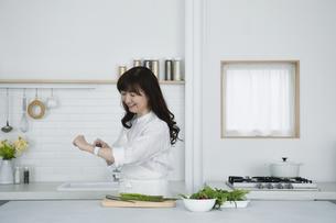 キッチンに立つ女性の写真素材 [FYI04303731]