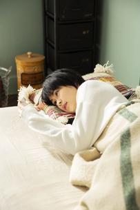 部屋で寝転がる20代女性の写真素材 [FYI04303770]