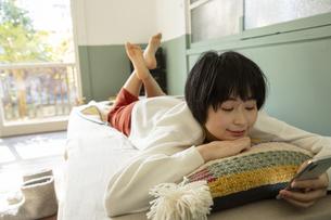 ベッドに寝転がりスマホを操作する20代女性の写真素材 [FYI04303808]