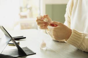 マニキュアを塗る女性の手元の写真素材 [FYI04303835]