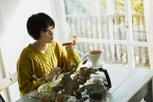 パンを食べる20代女性の写真素材 [FYI04303841]