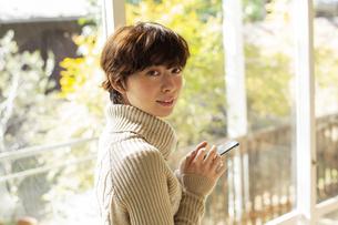 窓際でスマホを操作する20代女性の写真素材 [FYI04303852]