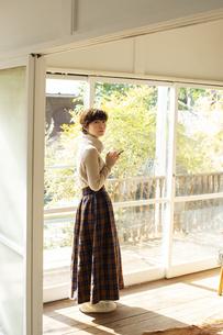 窓際でスマホを操作する20代女性の写真素材 [FYI04303853]