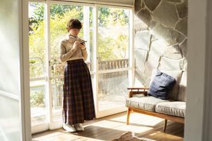 窓際でスマホを操作する20代女性の写真素材 [FYI04303854]