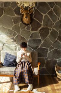 窓際でスマホを操作する20代女性の写真素材 [FYI04303855]