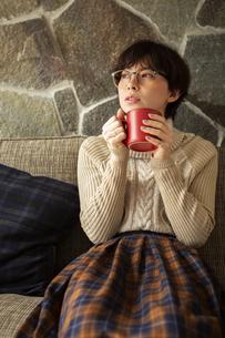 窓際でホットドリンクを飲む20代女性の写真素材 [FYI04303857]