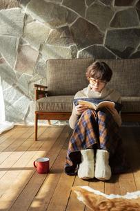 窓際で読書を楽しむ20代女性の写真素材 [FYI04303861]