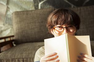 窓際で読書を楽しむ20代女性の写真素材 [FYI04303865]