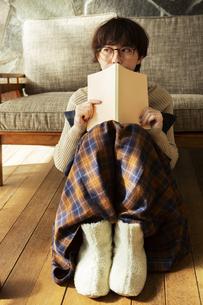 窓際で読書を楽しむ20代女性の写真素材 [FYI04303866]