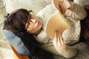 ソファに寝転がり読書を楽しむ20代女性の写真素材 [FYI04303868]