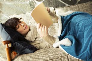 ソファに寝転がり読書を楽しむ20代女性の写真素材 [FYI04303870]