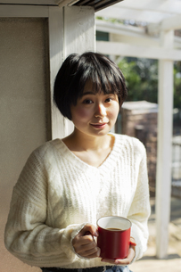 ホットドリンクを持つ20代女性の写真素材 [FYI04303889]