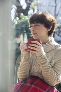 縁側でホットドリンクを飲む20代女性の写真素材 [FYI04303893]