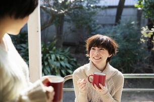 縁側でホットドリンクを飲む20代女性2人の写真素材 [FYI04303895]