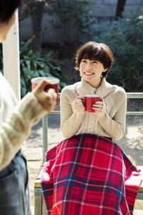 縁側でホットドリンクを飲む20代女性2人の写真素材 [FYI04303896]