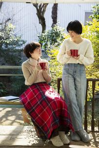 縁側でホットドリンクを飲む20代女性2人の写真素材 [FYI04303897]