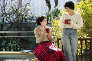 縁側でホットドリンクを飲む20代女性2人の写真素材 [FYI04303898]