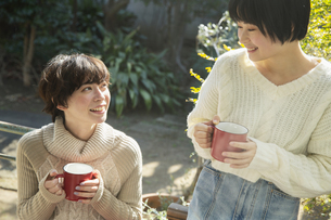 縁側でホットドリンクを飲む20代女性2人の写真素材 [FYI04303899]