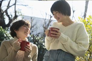 縁側でホットドリンクを飲む20代女性2人の写真素材 [FYI04303900]