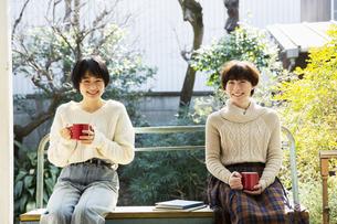 縁側でホットドリンクを飲む20代女性2人の写真素材 [FYI04303902]