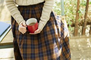 縁側でカップを持つ女性の手元の写真素材 [FYI04303906]
