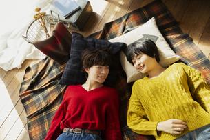 部屋で寝転がる20代女性2人の写真素材 [FYI04303936]