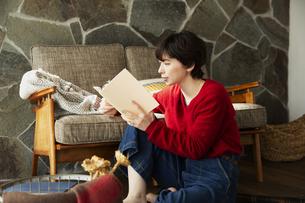 窓際に座り本を読む20代女性の写真素材 [FYI04303947]