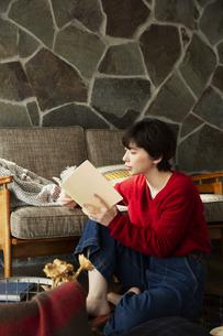 窓際に座り本を読む20代女性の写真素材 [FYI04303948]