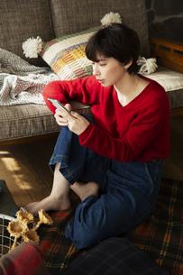窓際に座りスマホを操作する20代女性の写真素材 [FYI04303949]