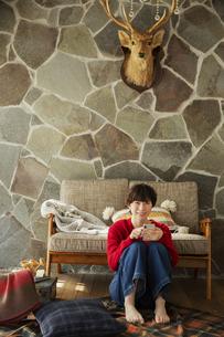 窓際に座りスマホを操作する20代女性の写真素材 [FYI04303954]