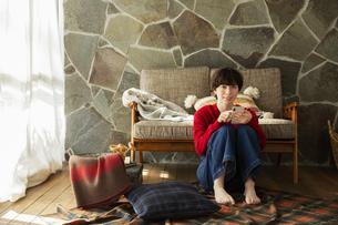 窓際に座りスマホを操作する20代女性の写真素材 [FYI04303958]