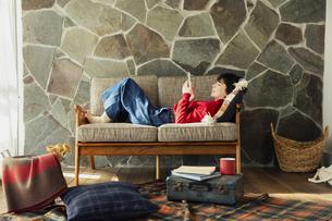 ソファに寝転がり読書を楽しむ20代女性の写真素材 [FYI04303959]
