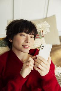 ソファに寝転がりスマホを操作する20代女性の写真素材 [FYI04303962]