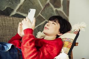 ソファに寝転がりスマホを操作する20代女性の写真素材 [FYI04303963]