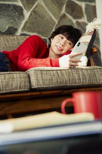 ソファに寝転がりスマホを操作する20代女性の写真素材 [FYI04303996]