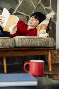ソファに寝転がり読書を楽しむ20代女性の写真素材 [FYI04303997]