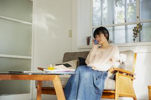 部屋で電話をする20代女性の写真素材 [FYI04304021]