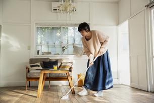 部屋の掃除をする20代女性の写真素材 [FYI04304028]