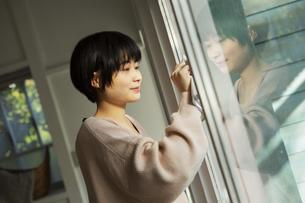 窓拭きをする20代女性の写真素材 [FYI04304032]
