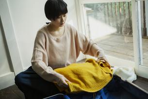 キャリーバックに洋服を入れる20代女性の写真素材 [FYI04304035]