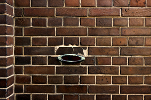 古いレンガ造りの壁に開けられたアンティークなデザインの郵便受けの投入口の写真素材 [FYI04305194]