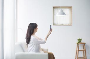 ソファに座る女性スマートフォンと女性の写真素材 [FYI04305232]