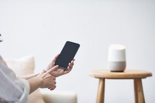 スマートスピーカーとスマートフォンと女性の手の写真素材 [FYI04305244]