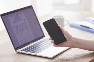 スマートフォンとノートパソコンと女性の手の写真素材 [FYI04305265]