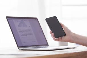 スマートフォンとノートパソコンと女性の手の写真素材 [FYI04305266]