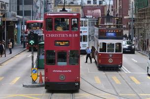 香港の街を行く路面電車トラム。英国植民地時代から走り続ける香港庶民の足。右のオープンデッキのトラムは観光客向けの「トラム・ツアー」の車両の写真素材 [FYI04305525]
