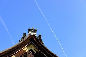 屋根と飛行機雲の写真素材 [FYI04305668]