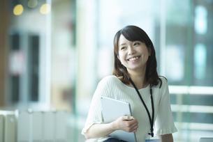 タブレットを持ち微笑む女性社員の写真素材 [FYI04305738]