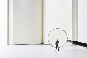 虫眼鏡で本を読むビジネスマンの写真素材 [FYI04306019]