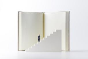 本を読む階段の上のビジネスマンの写真素材 [FYI04306021]